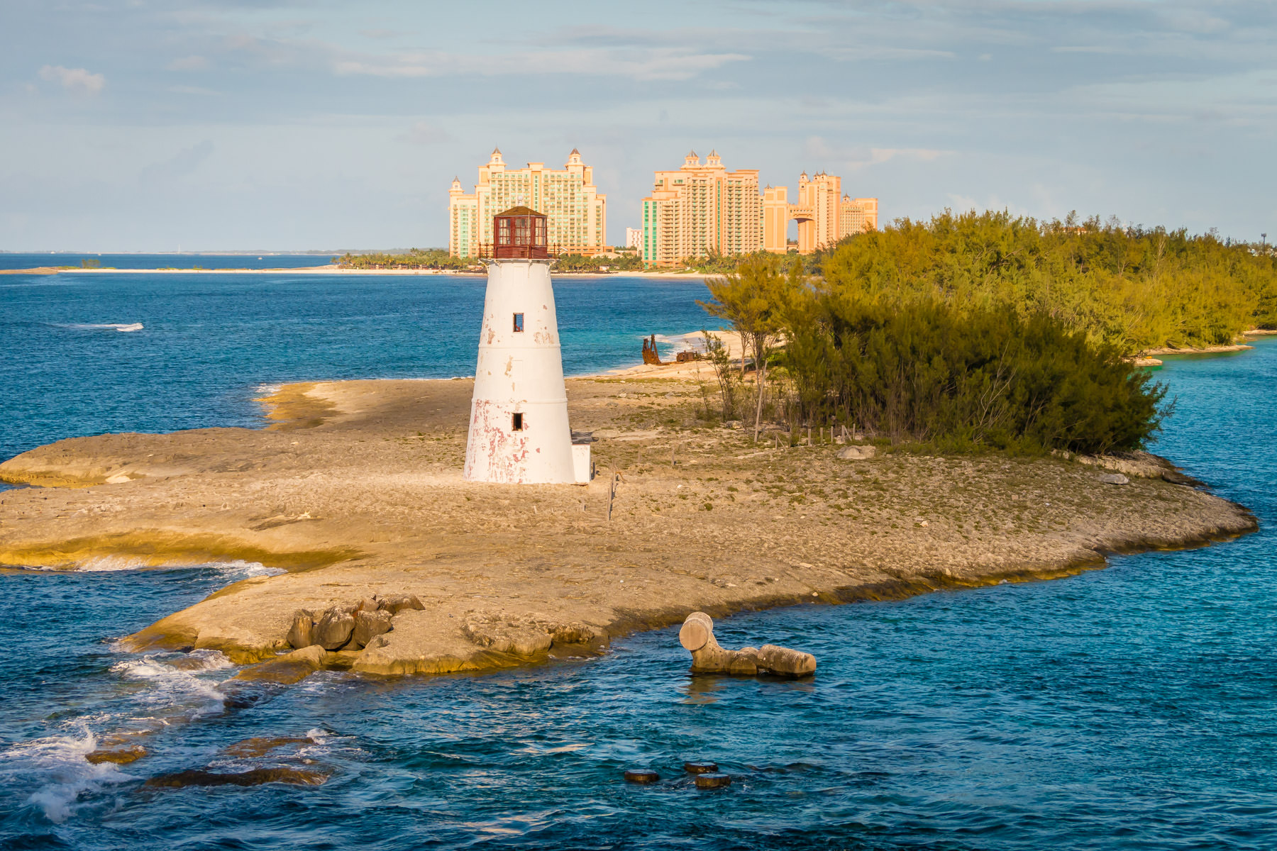 The Nassau Harbour Lighthouse sits abandoned on the western end of Colonial Beach as the Atlantis mega-resort rises in the background.