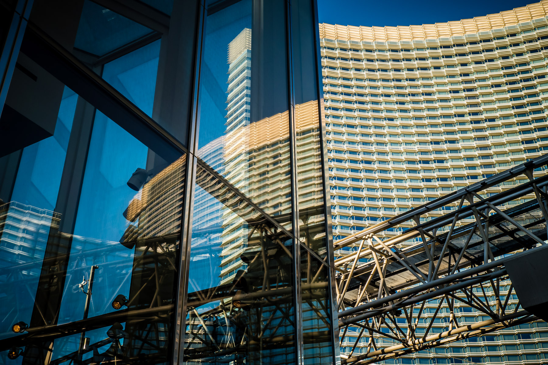 The track for the CityCenter tram, reflected in the lobby windows of one of the Veer Towers as the Aria rises into the background at CityCenter, Las Vegas.