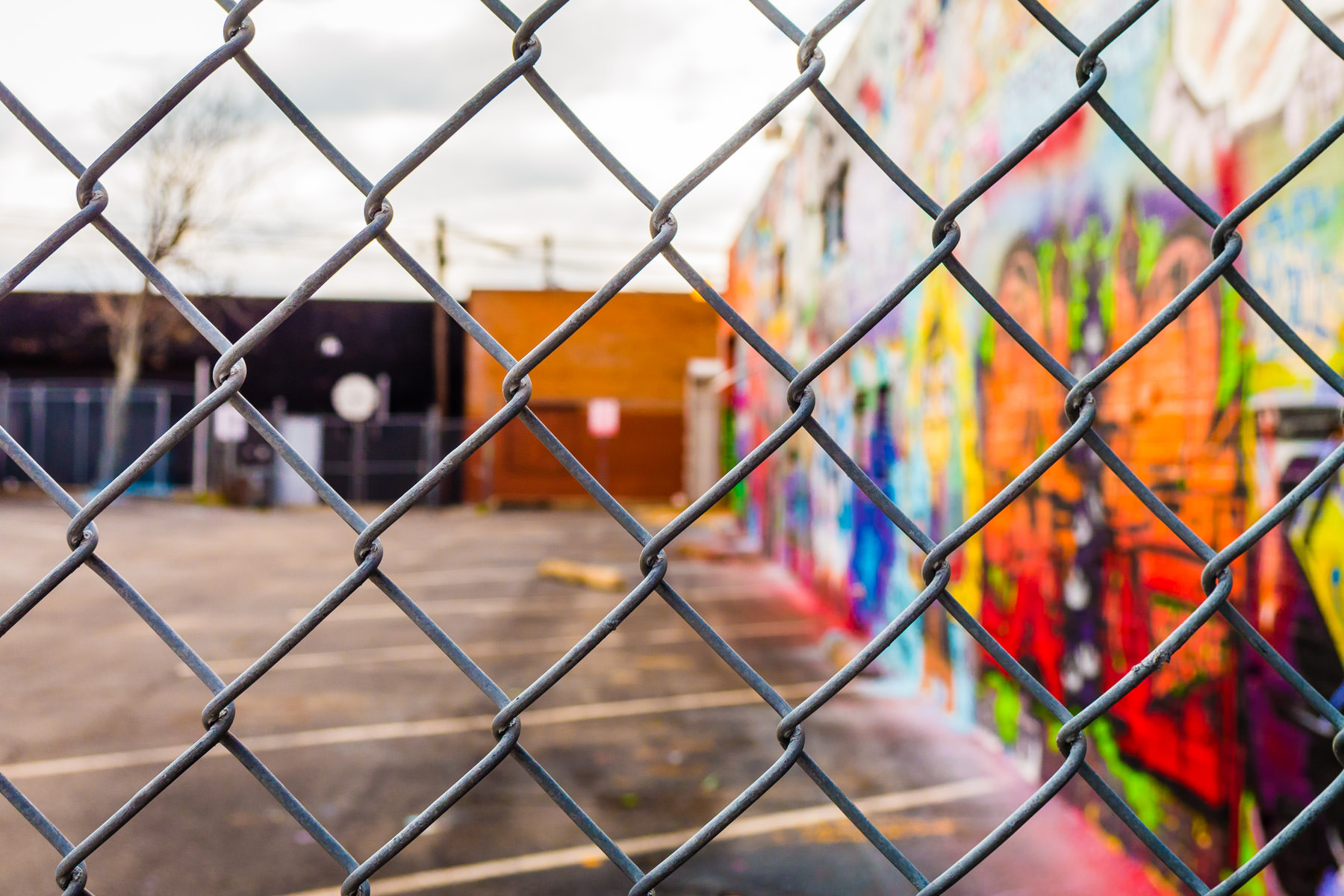 A wall covered with a graffiti mural adjacent to a fenced-in parking lot in Dallas' Deep Ellum neighborhood.