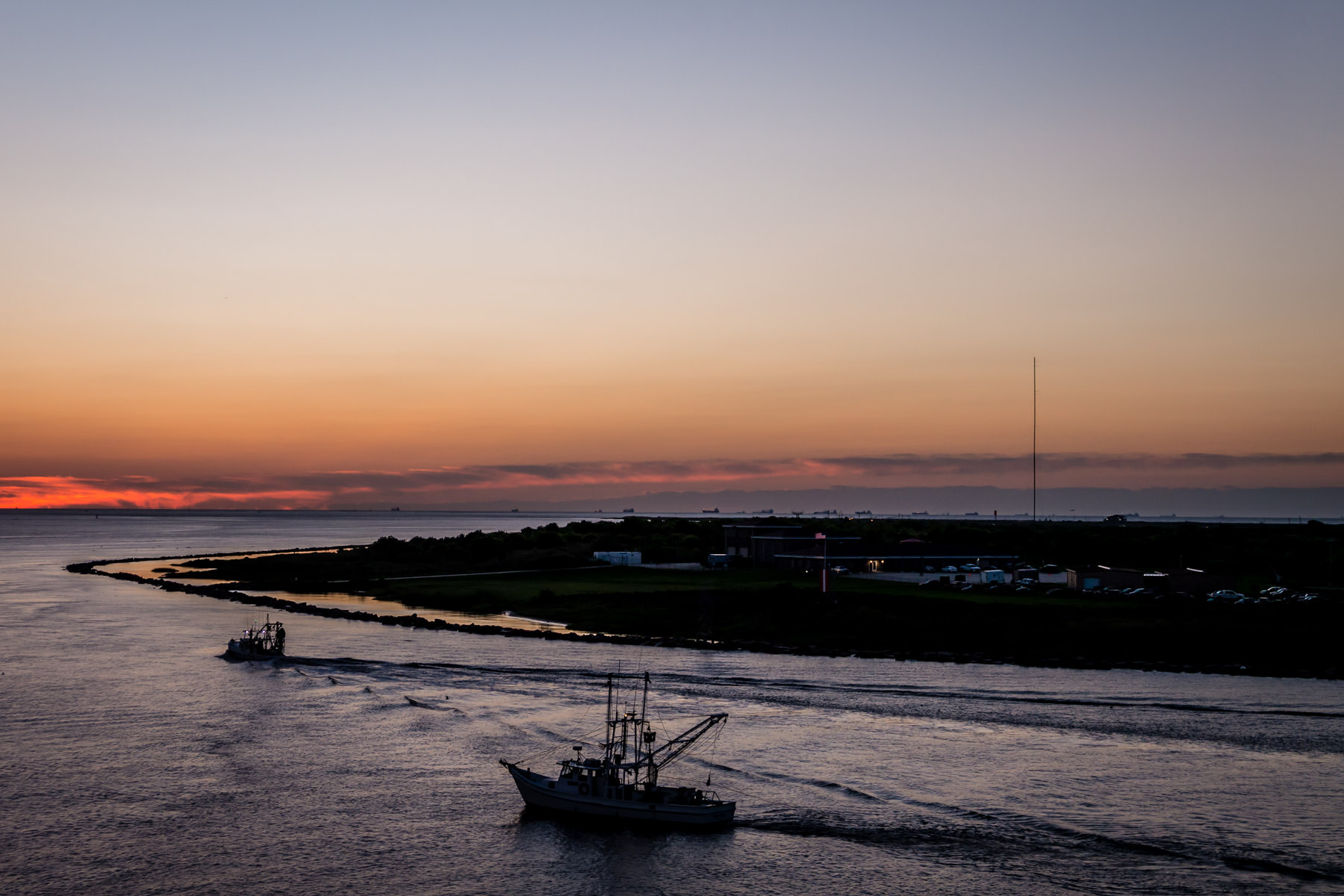 Shrimp boats head out into the Gulf of Mexico as dawn breaks over Galveston Island, Texas.