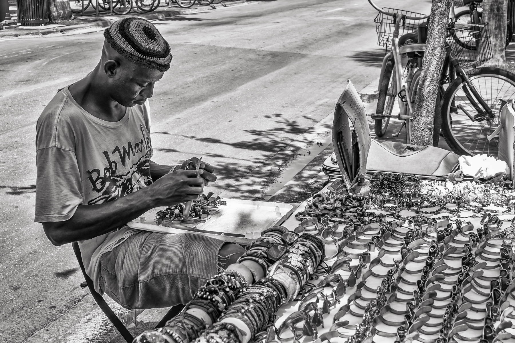 A street vendor crafts and sells bracelets in Key West, Florida.