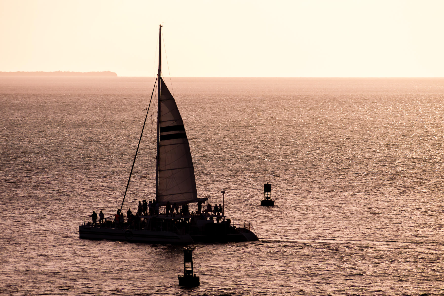 A catamaran sailboat is backlit by the late-afternoon sun just off the coast of Key West, Florida.