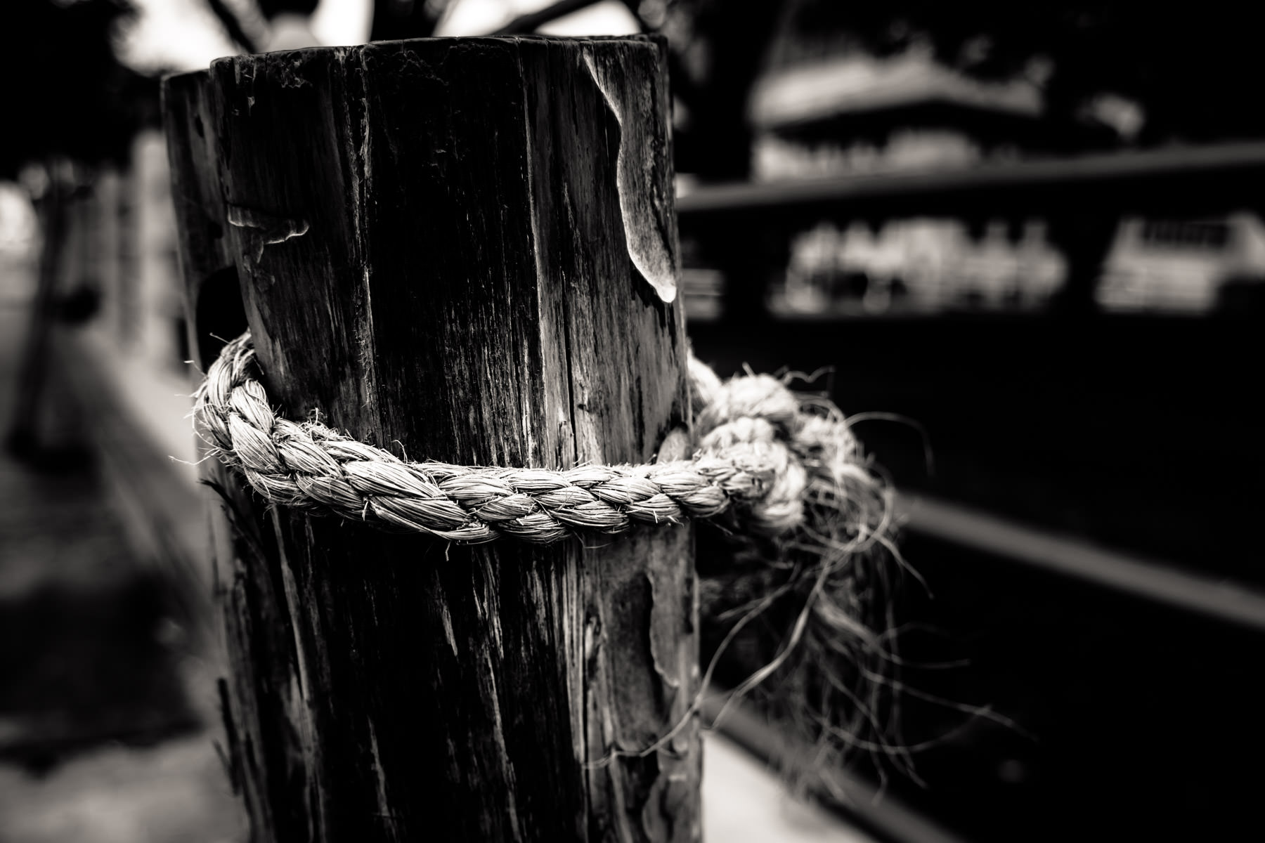 A rough rope tied around a wooden post to make a temporary fence at the Fort Worth Stockyards.