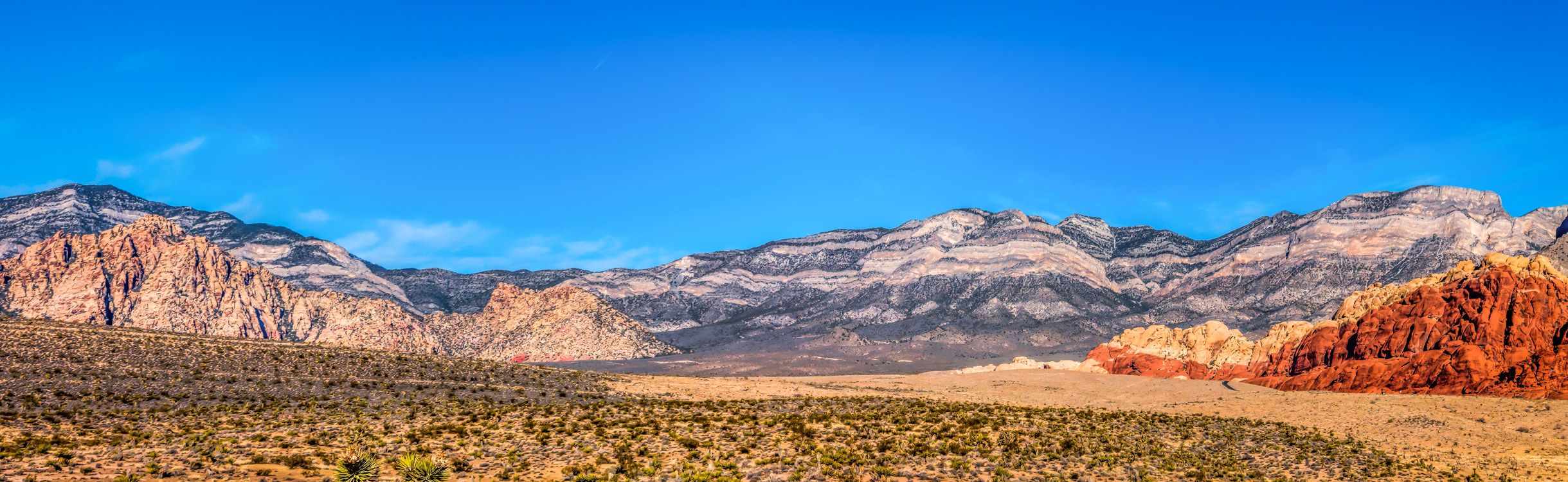 A sweeping panorama of the desert landscape of Nevada's Red Rock Canyon National Conservation Area.