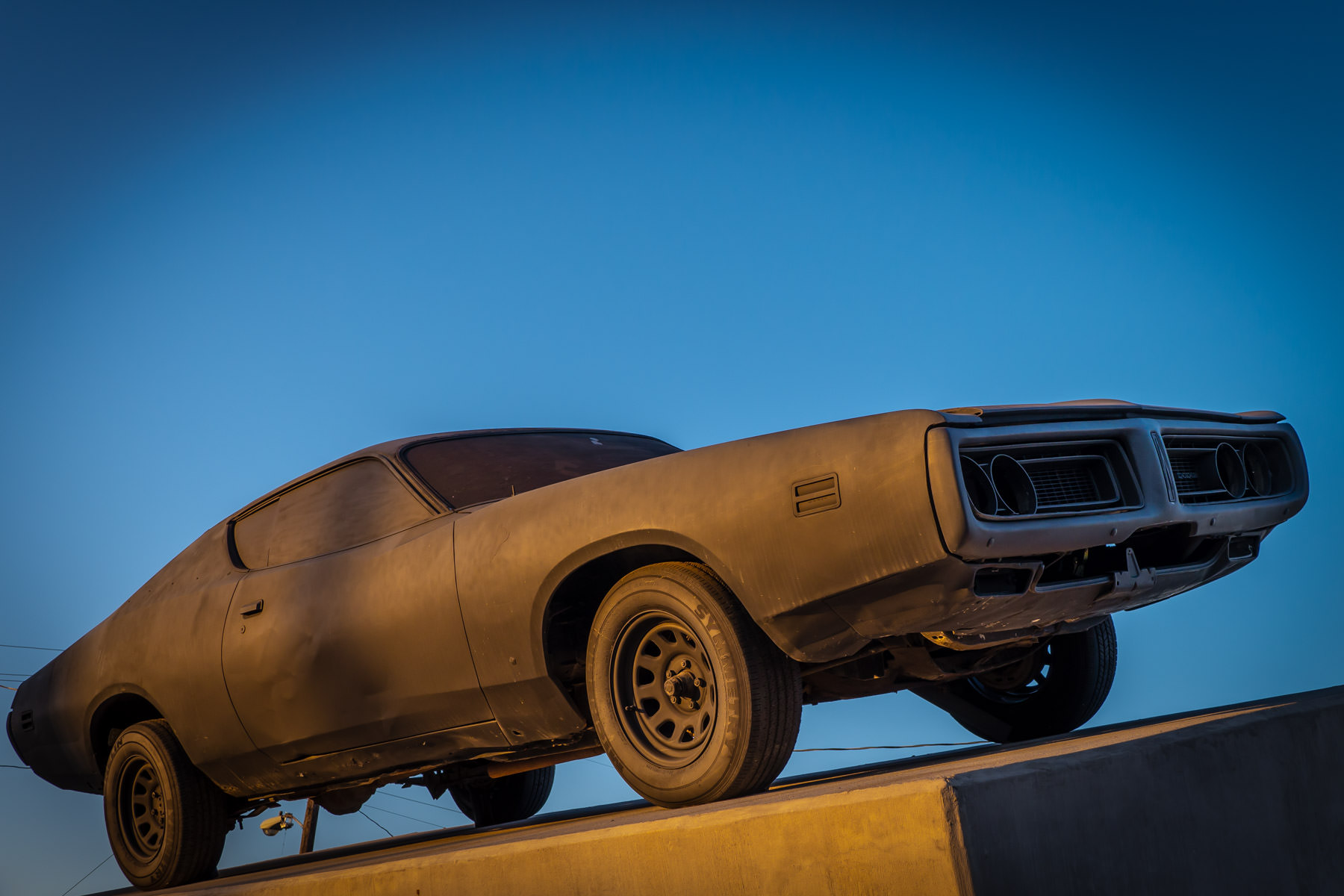 A matte-black 1972 Dodge Charger sits atop a canted concrete platform as part of sculpture Richard Phillips' collaboration with Playboy. Originally sited in Marfa, Texas, the sculpture now resides at the Dallas Contemporary.