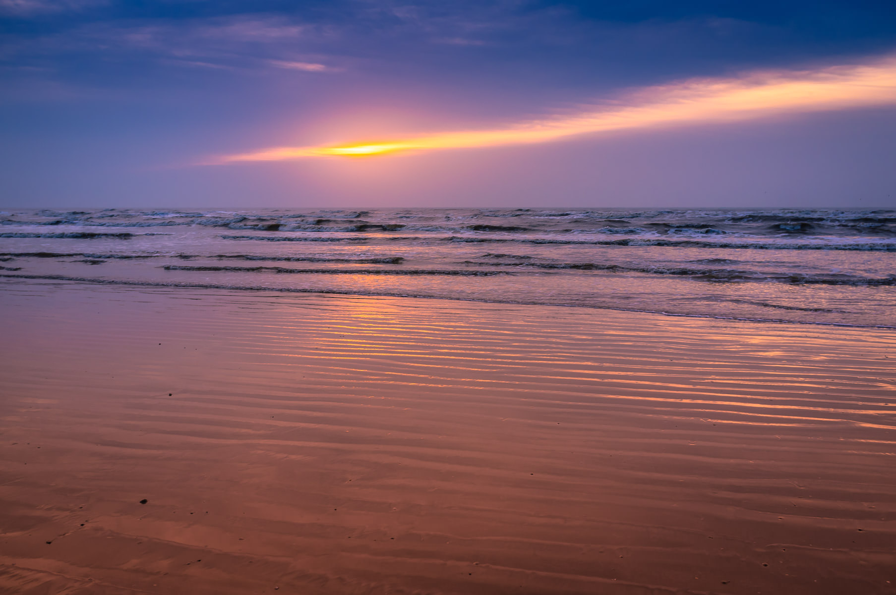 The sun rises over the Gulf of Mexico, shining through the early-morning clouds at Galveston, Texas.