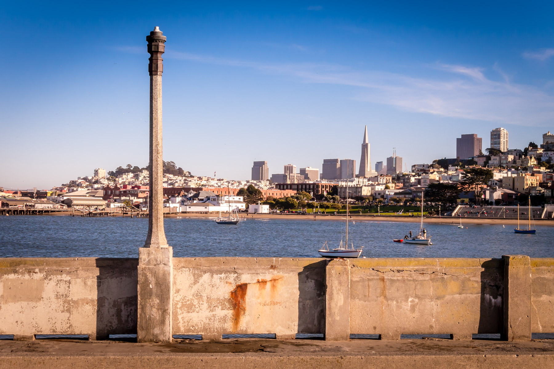 A light pole on San Francisco's crumbling Aquatic Park Pier rises in front of the city's iconic skyline.