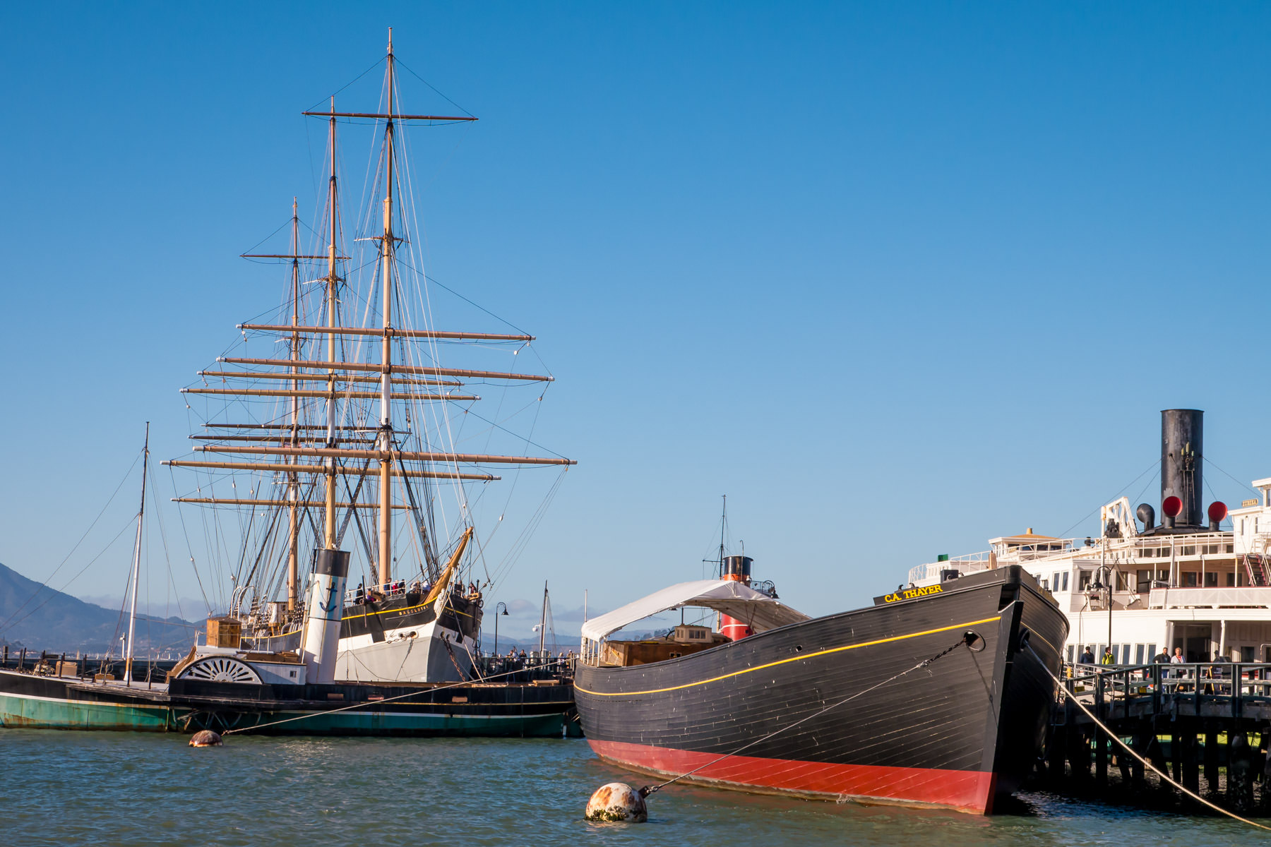 A few of the historic boats, including the 1885 lumber schooner C.A. Thayer, the 1914 paddlewheel tugboat Eppleton Hall and the 1886 square rigged Balclutha, on display at the San Francisco Maritime National Historical Park.