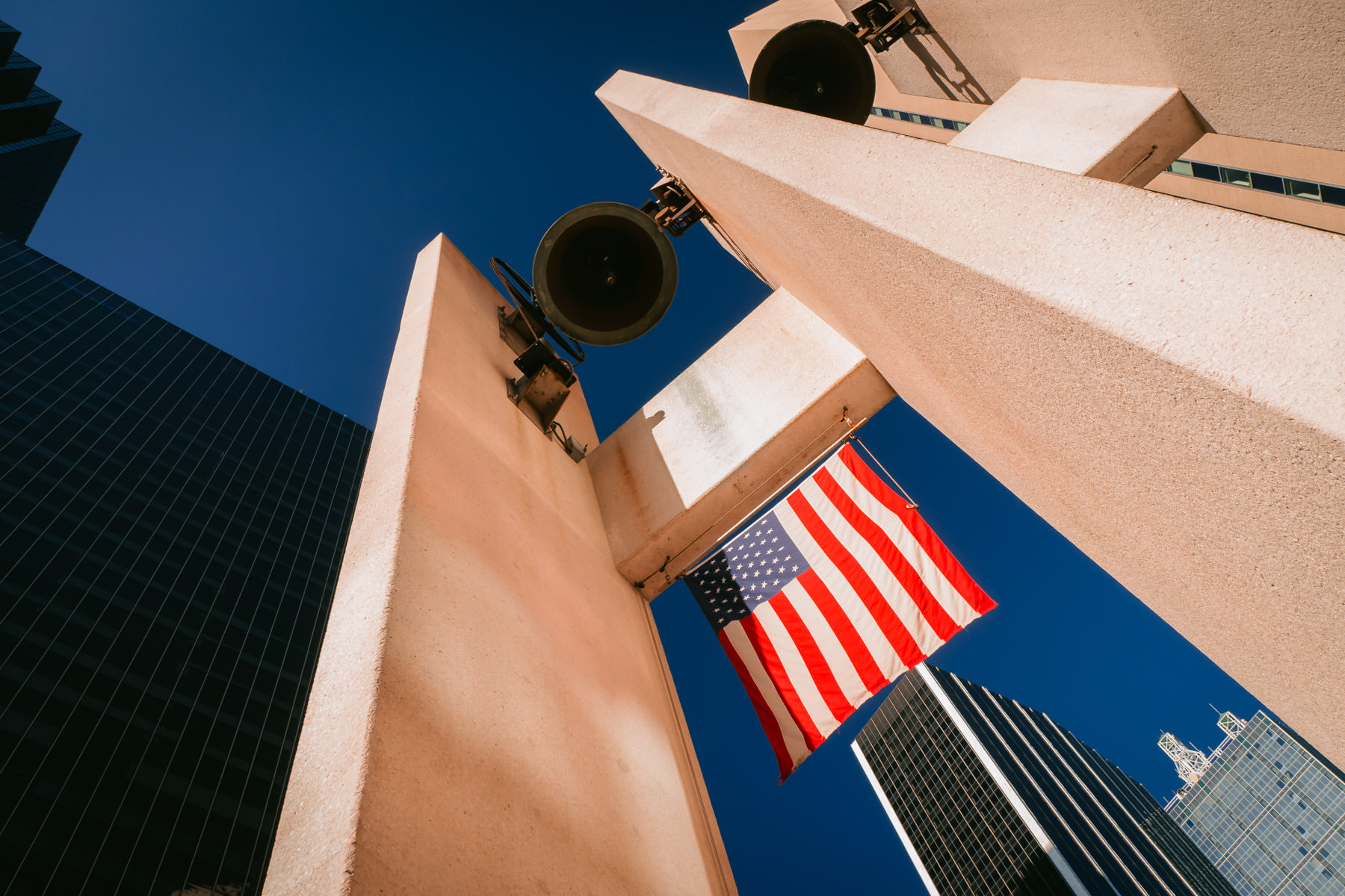An American flag hangs among the skyscrapers of Downtown Dallas at Thanks-Giving Square.
