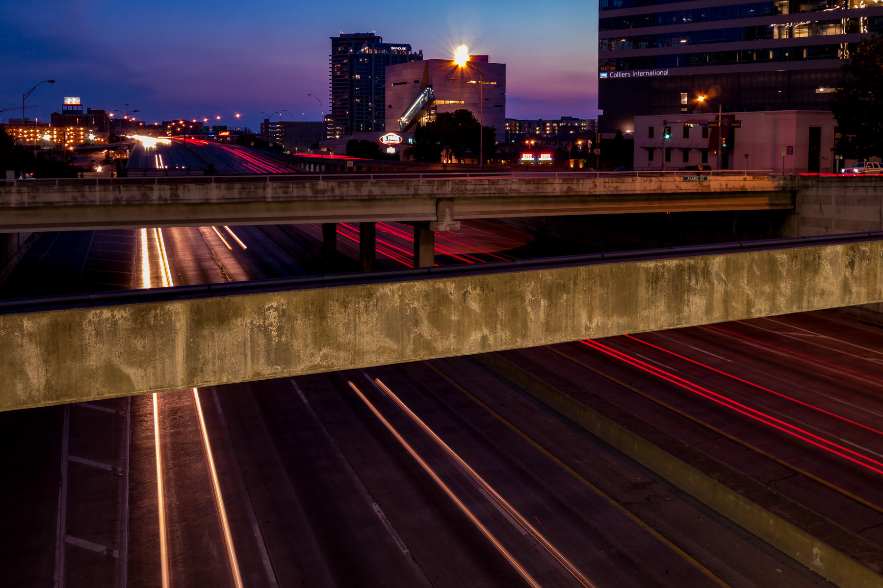 Steady traffic streams through the Downtown Dallas' Woodall Rodgers Freeway as night descends on North Texas.