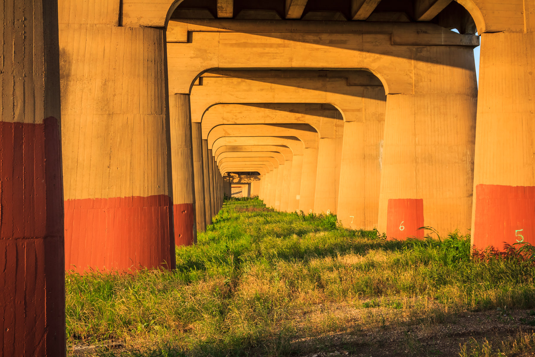 The setting sun illuminates the repeating pattern of Dallas' Continental Avenue Bridge's cast concrete support legs recedes into the distance.