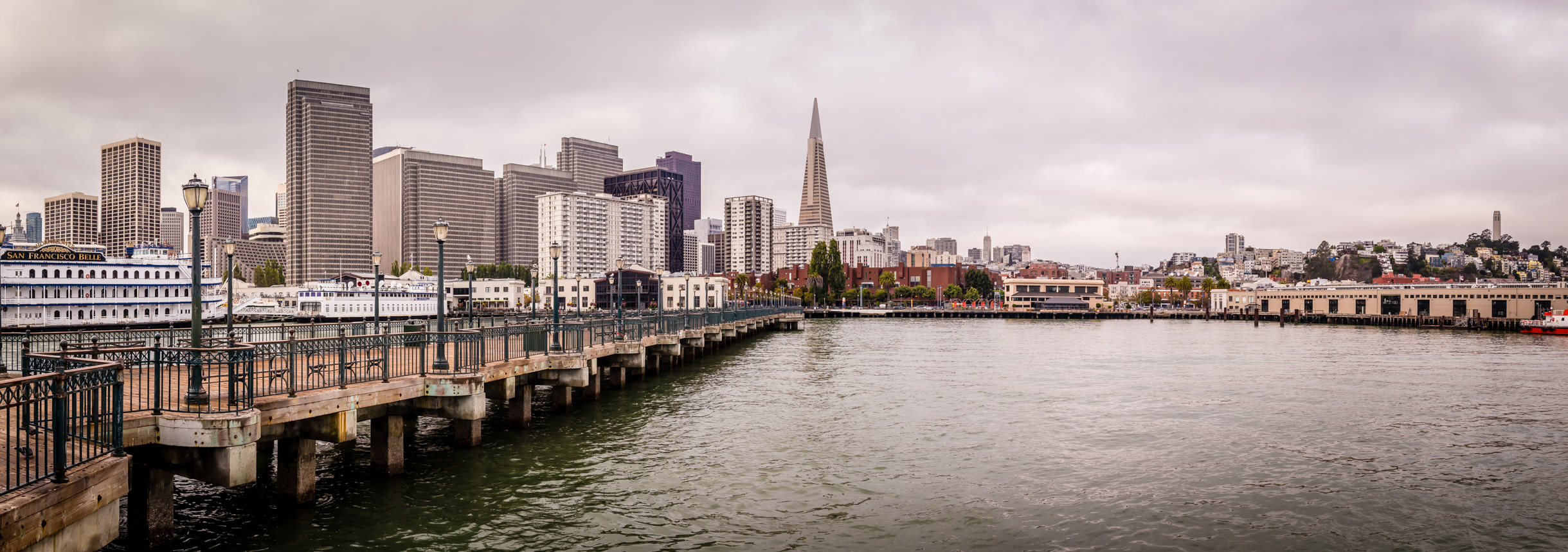 A panoramic view of San Francisco's Financial District and Telegraph Hill on a cloudy day, as seen from Pier 7 along the Embarcadero.
