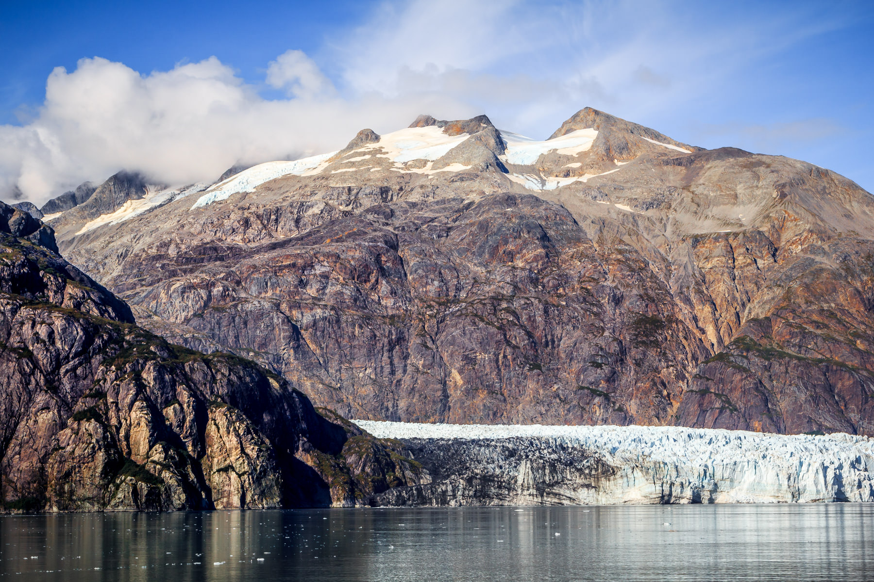 Lamplugh Glacier is dwarfed by 6,155 ft / 1,876 m tall Mount Cooper in Alaska's Glacier Bay.