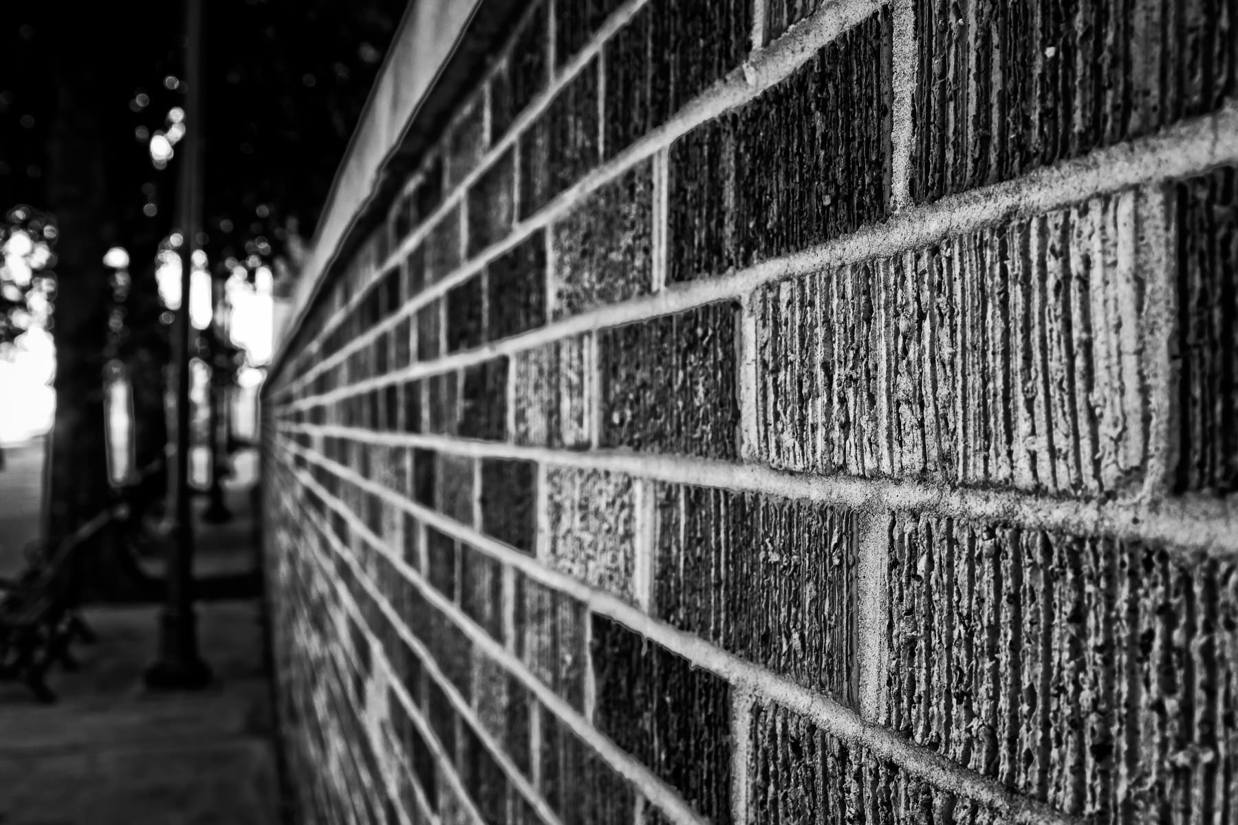 A brick wall recedes into the distance along a Downtown Tyler, Texas, sidewalk.