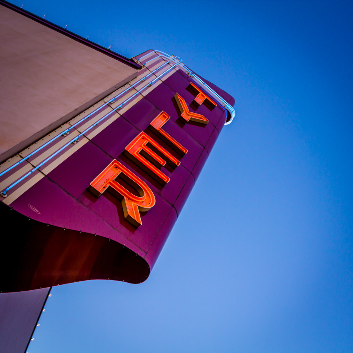 The newly-repaired sign of the long-closed Tyler Theater in Downtown Tyler, Texas, reaches into the early-evening sky.