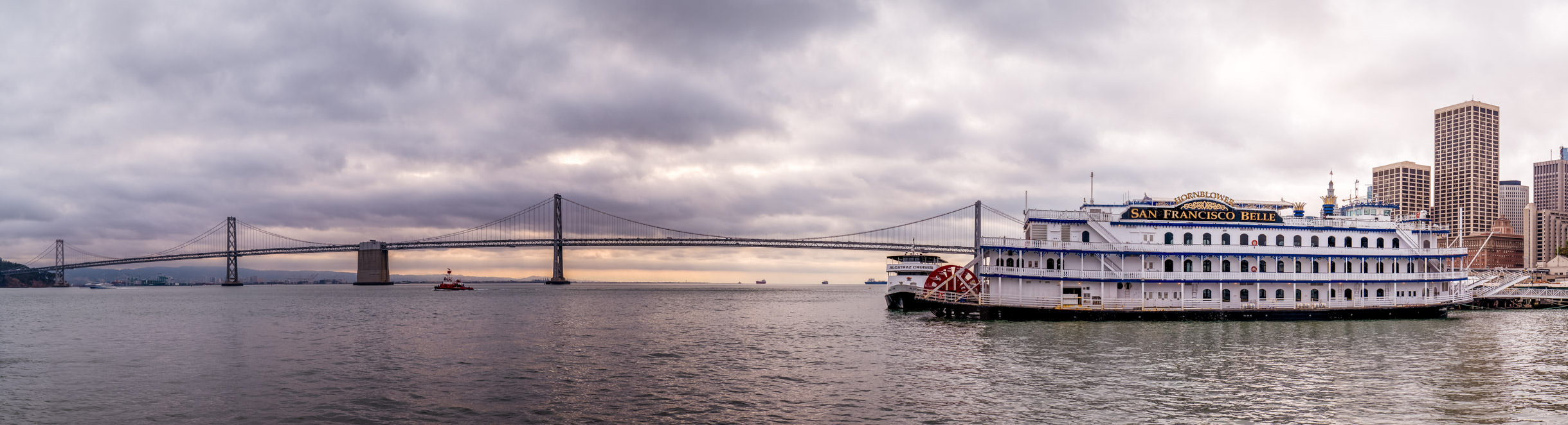 Hornblower Cruises' dining yacht San Francisco Belle sits docked along the city's waterfront as the Bay Bridge sweeps gracefully across the horizon as the sun begins to rise on the Bay Area.