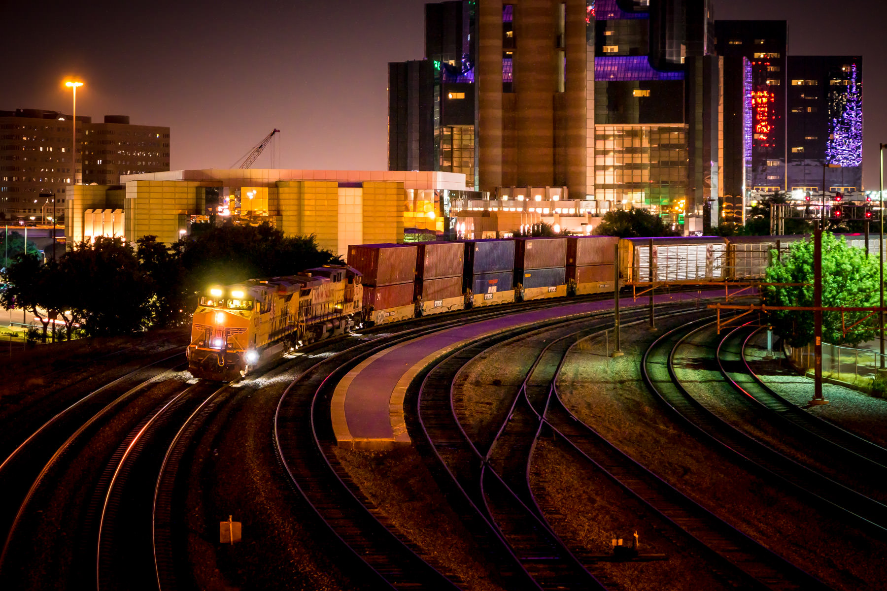 A Union Pacific train travels the rails near the Dallas Convention Center and Reunion Tower.