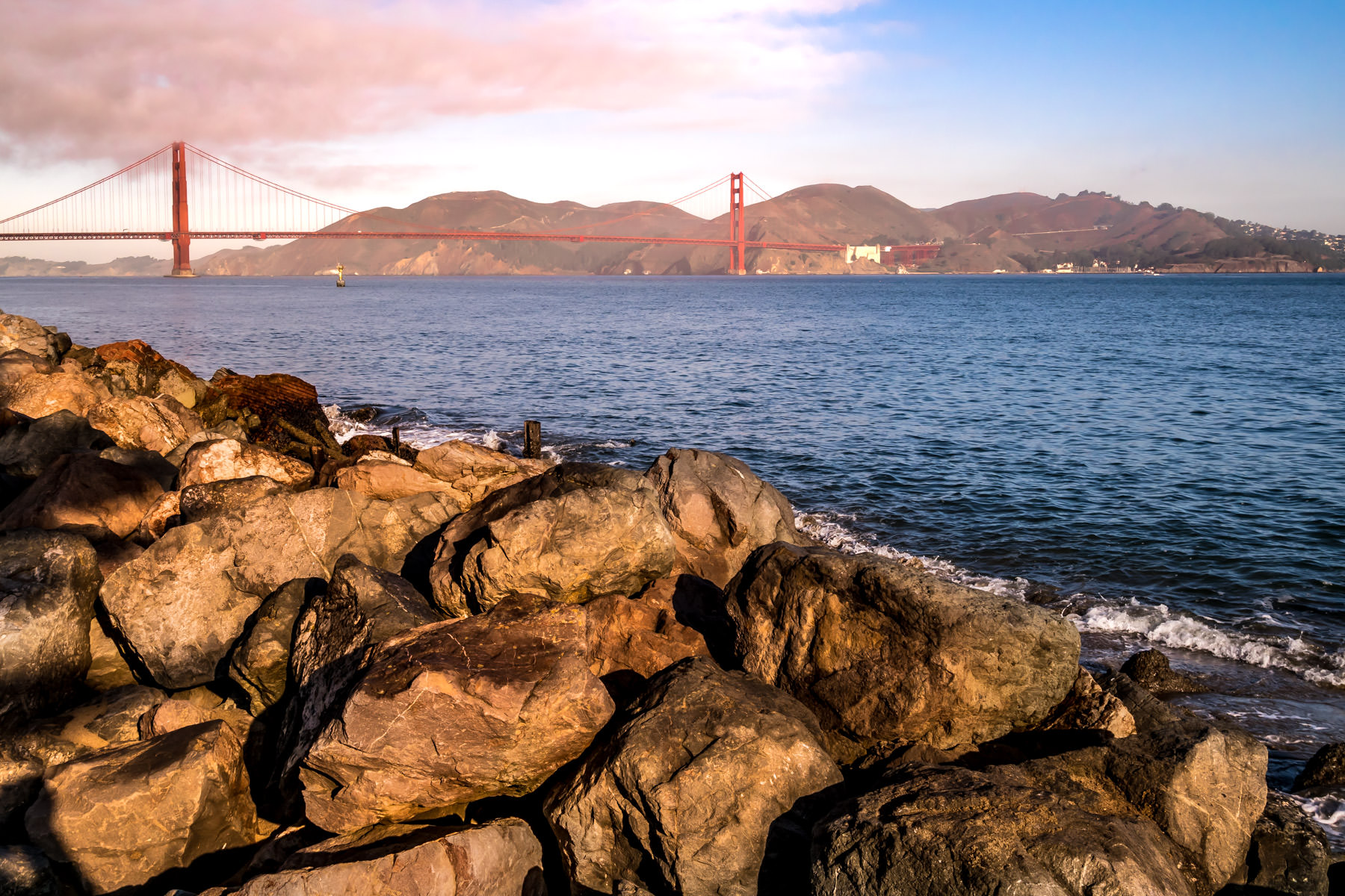 San Francisco's iconic Golden Gate Bridge spans its namesake narrows at the entrance to San Francisco Bay as seen from the rocky shoreline of nearby Crissy Field.