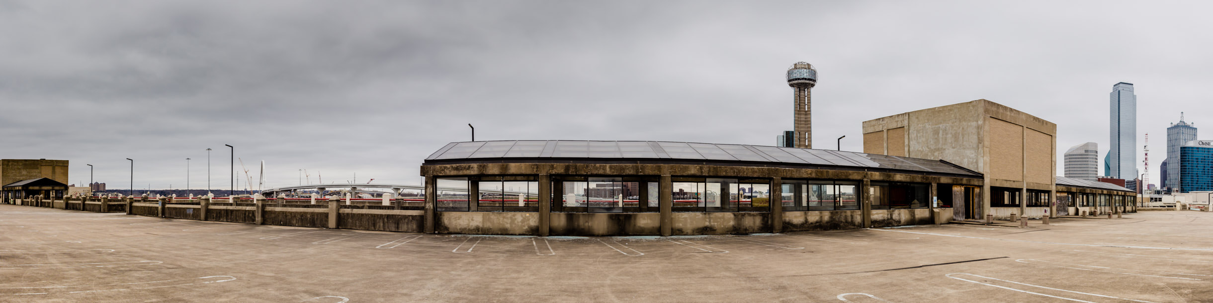 A panoramic view of the west end of the Downtown Dallas skyline as it rises over an abandoned parking garage originally built for the now-demolished Reunion Arena.