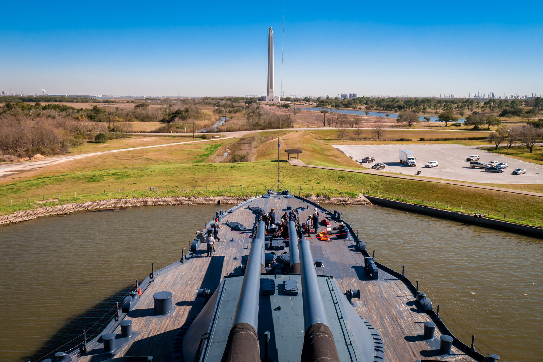 The main guns of the battleship USS Texas seem to aim at the nearby San Jacinto Monument as workers repair the wooden deck of the dreadnought, now docked as a museum ship near Houston.