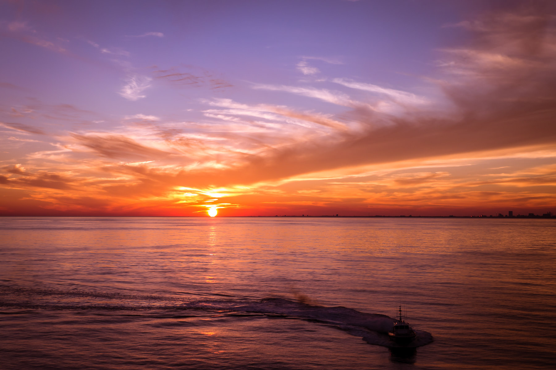The sun sets on the Gulf of Mexico near Bolivar Roads just off the coast of Galveston, Texas.