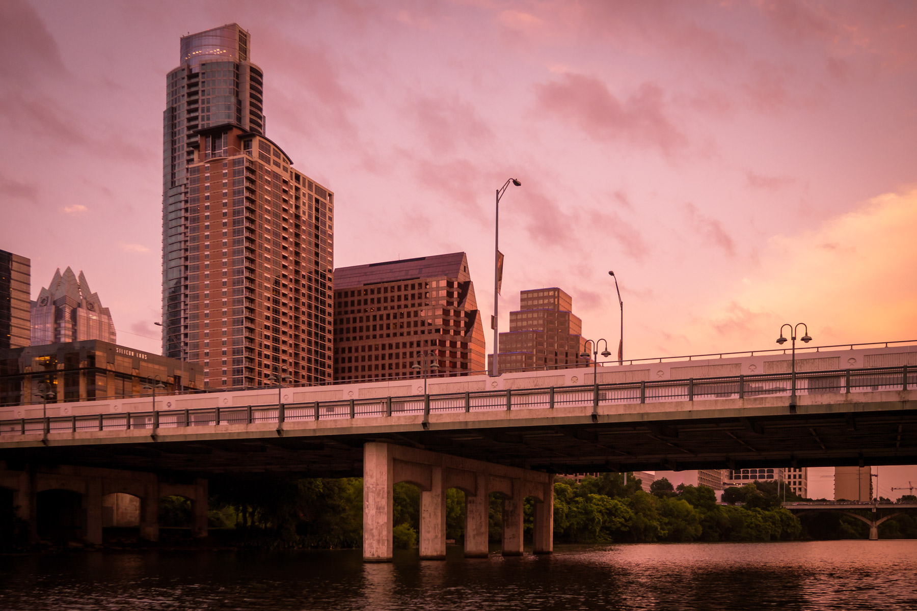 The sun sets on Downtown Austin and the South First Street Bridge as it spans Lady Bird Lake.