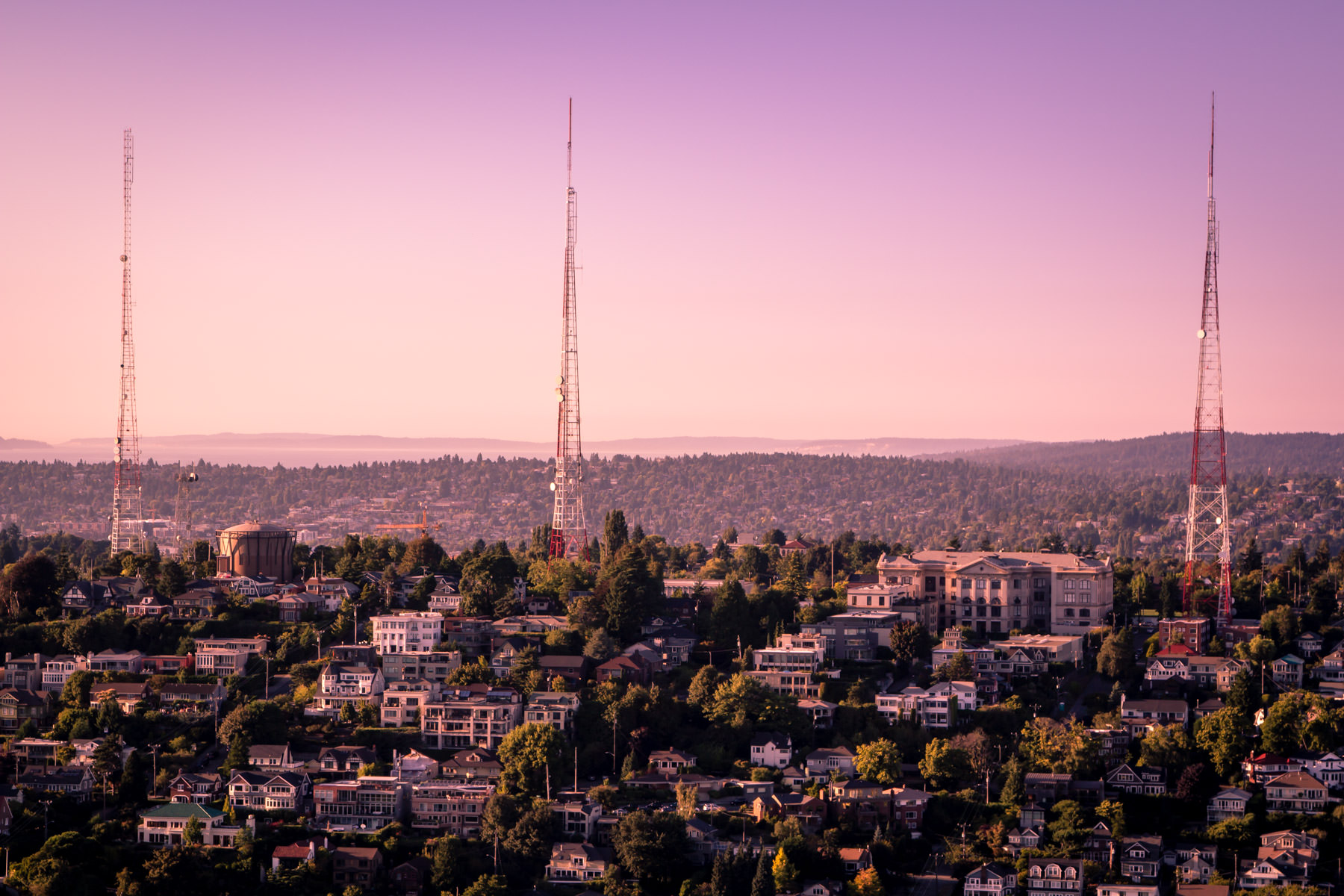Three broadcast towers rise into the sky as the sun sets on Seattle's Queen Anne neighborhood.