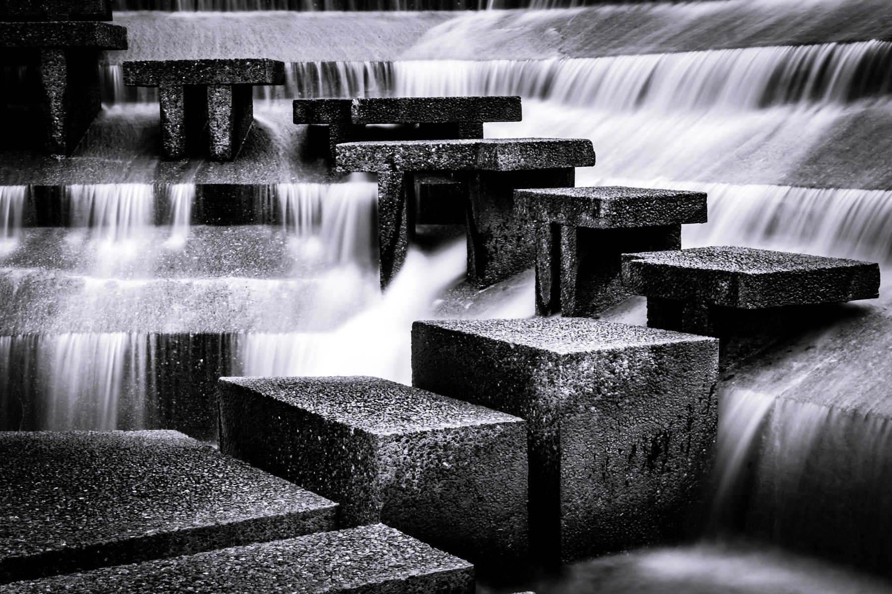 Water cascades around concrete steps at the Fort Worth Water Gardens.