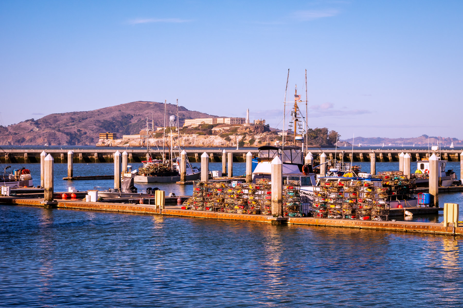 Dungeness crab fishing boats docked at a pier loaded with crab pots at Fisherman's Wharf in the shadow of San Francisco Bay's Alcatraz.