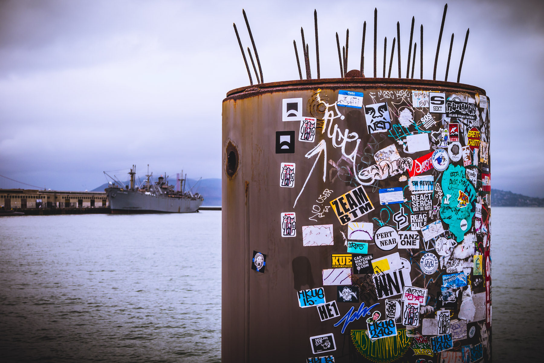 Decals cover a piece of dockside equipment on a cold, foggy morning at San Francisco's Fisherman's Wharf.