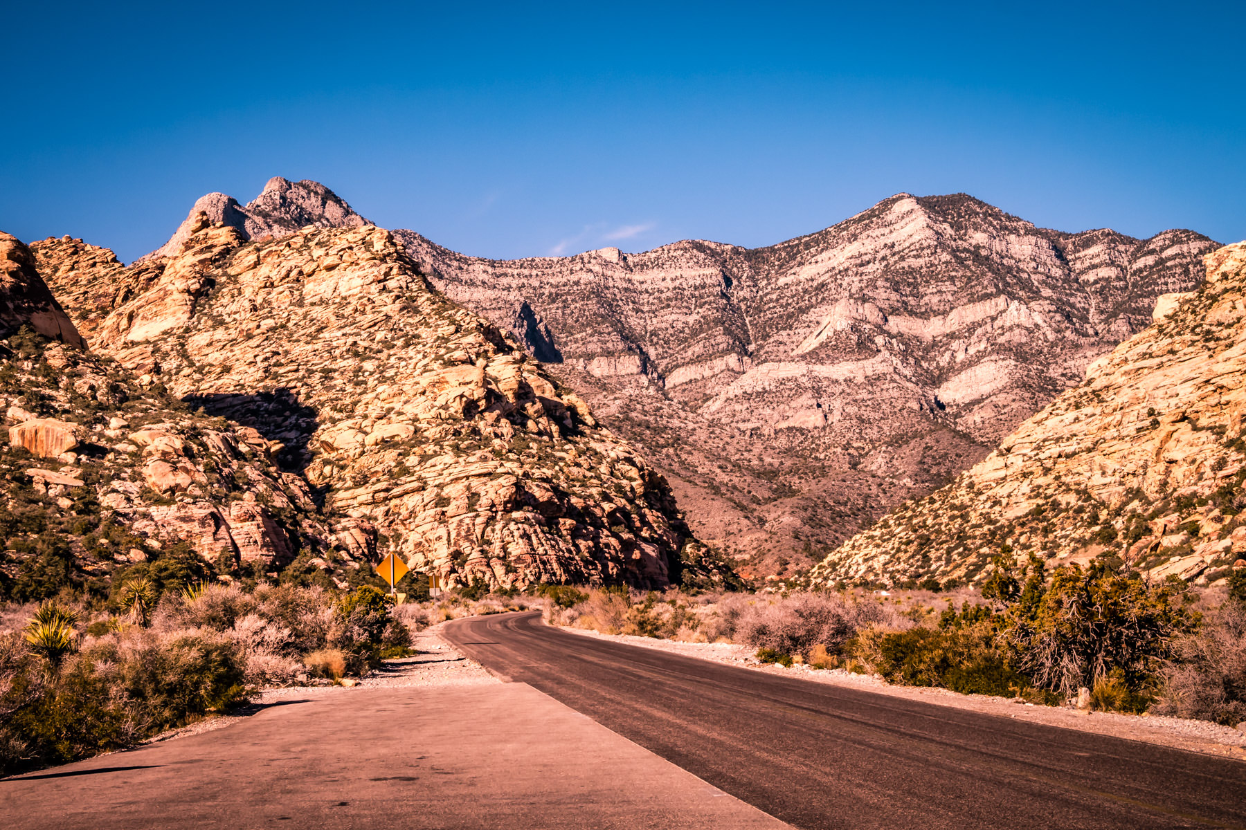 A road stretches through Nevada's Red Rock Canyon towards tall desert mountains.