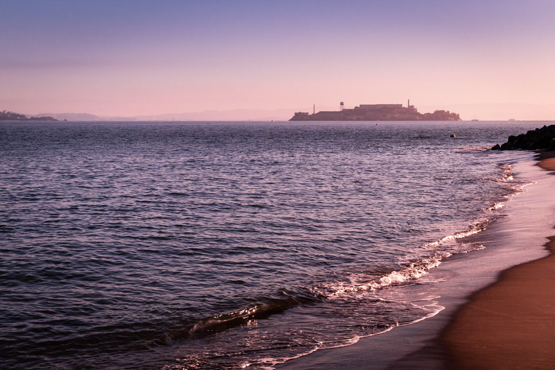 The morning sun lights Alcatraz and San Francisco Bay, as seen from the beach at the city's Crissy Field.