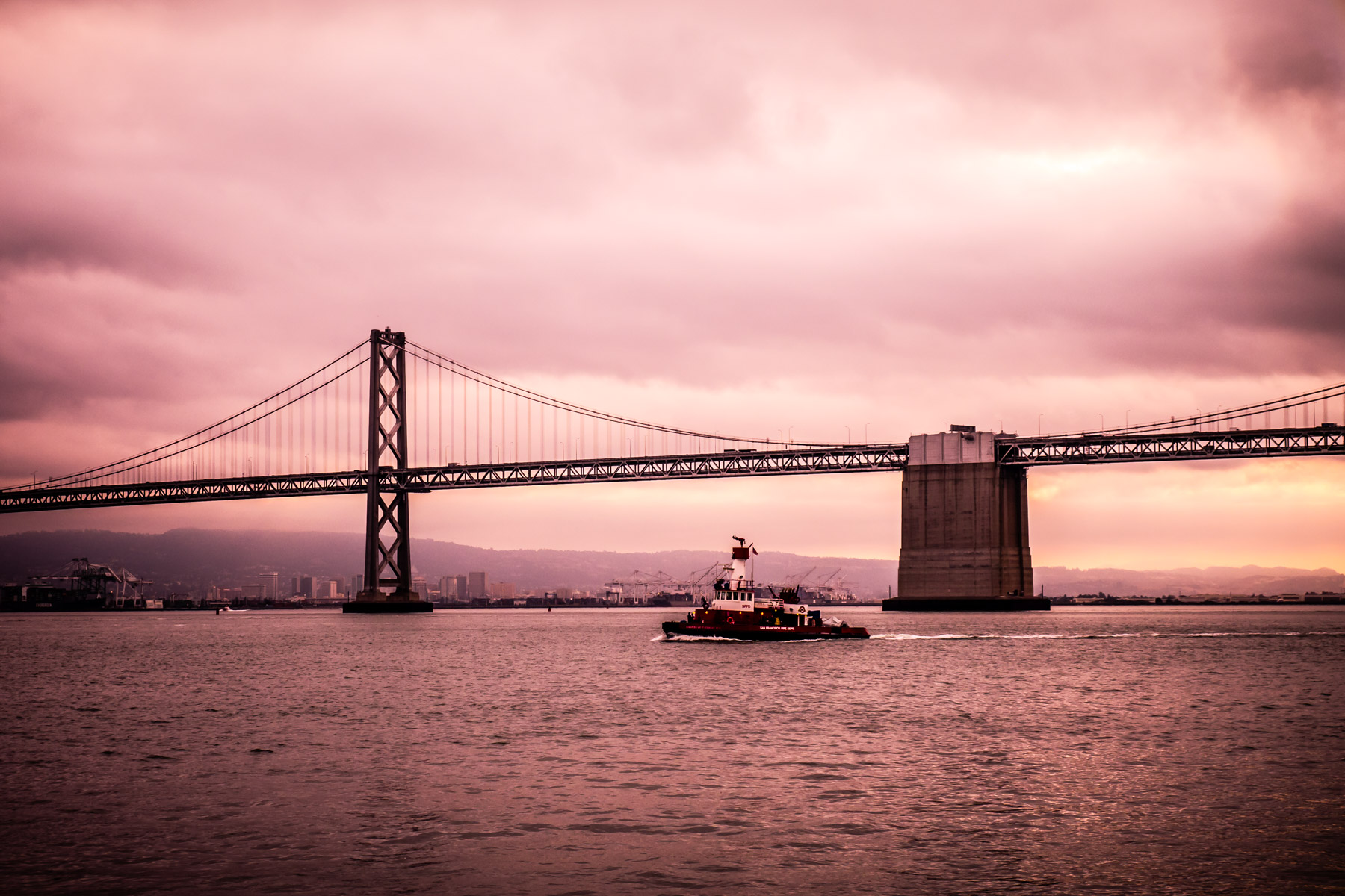 A San Francisco Fire Department boat traverses San Francisco Bay as the Bay Bridge rises to greet the morning sun.