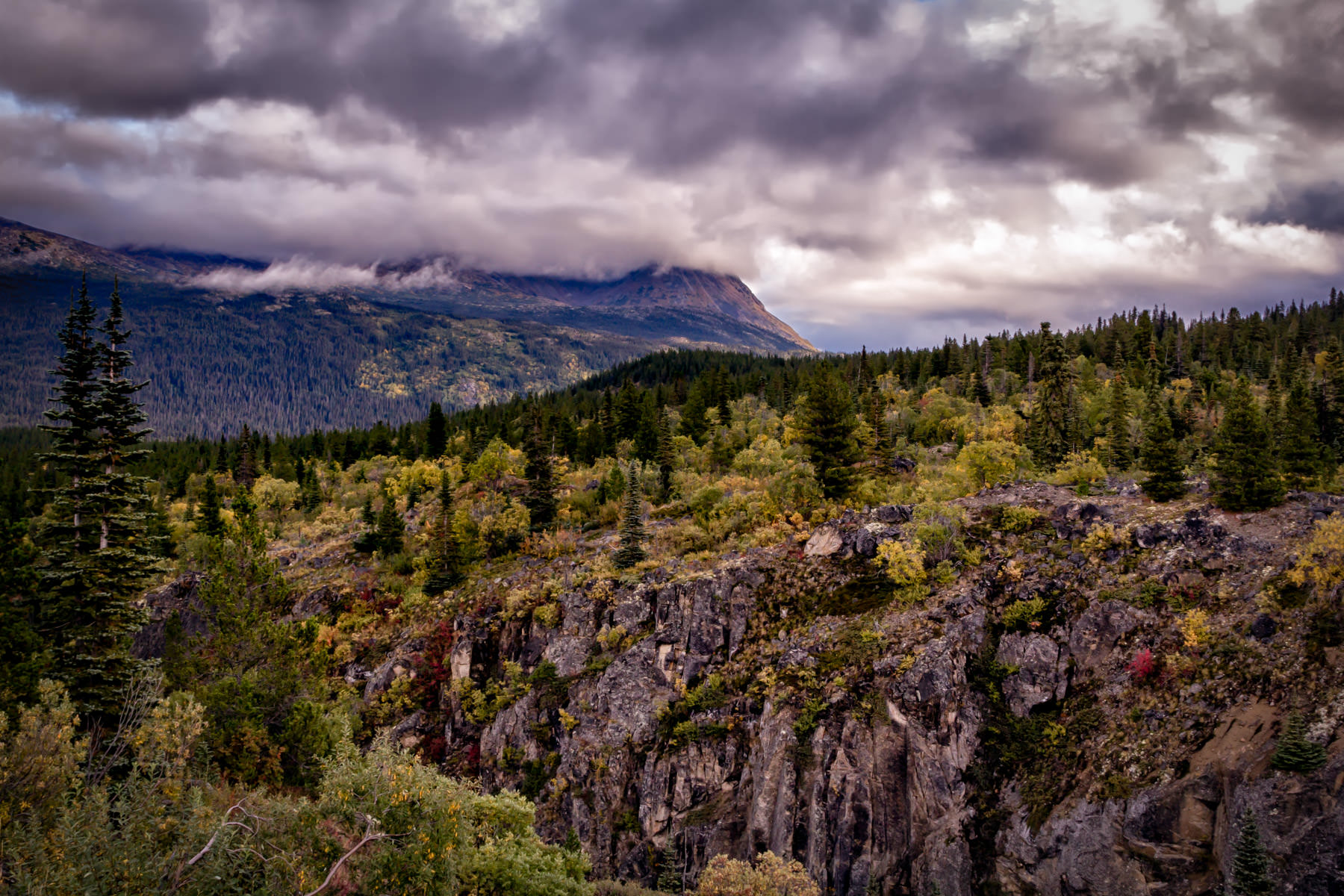 Dark clouds form over the forested mountains of British Columbia's Stikine Region.