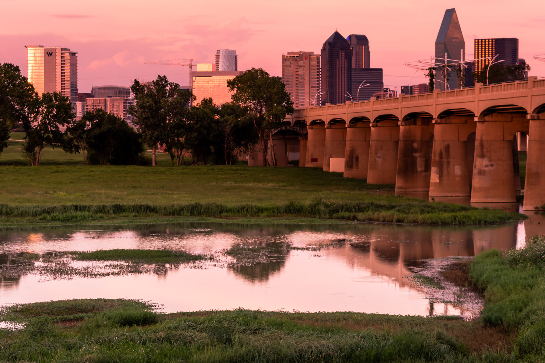 The Dallas skyline rises over the Trinity River bottoms at the far end of the Ronald Kirk Bridge park (formerly the Continental Avenue Bridge) as the sun sets on the city.