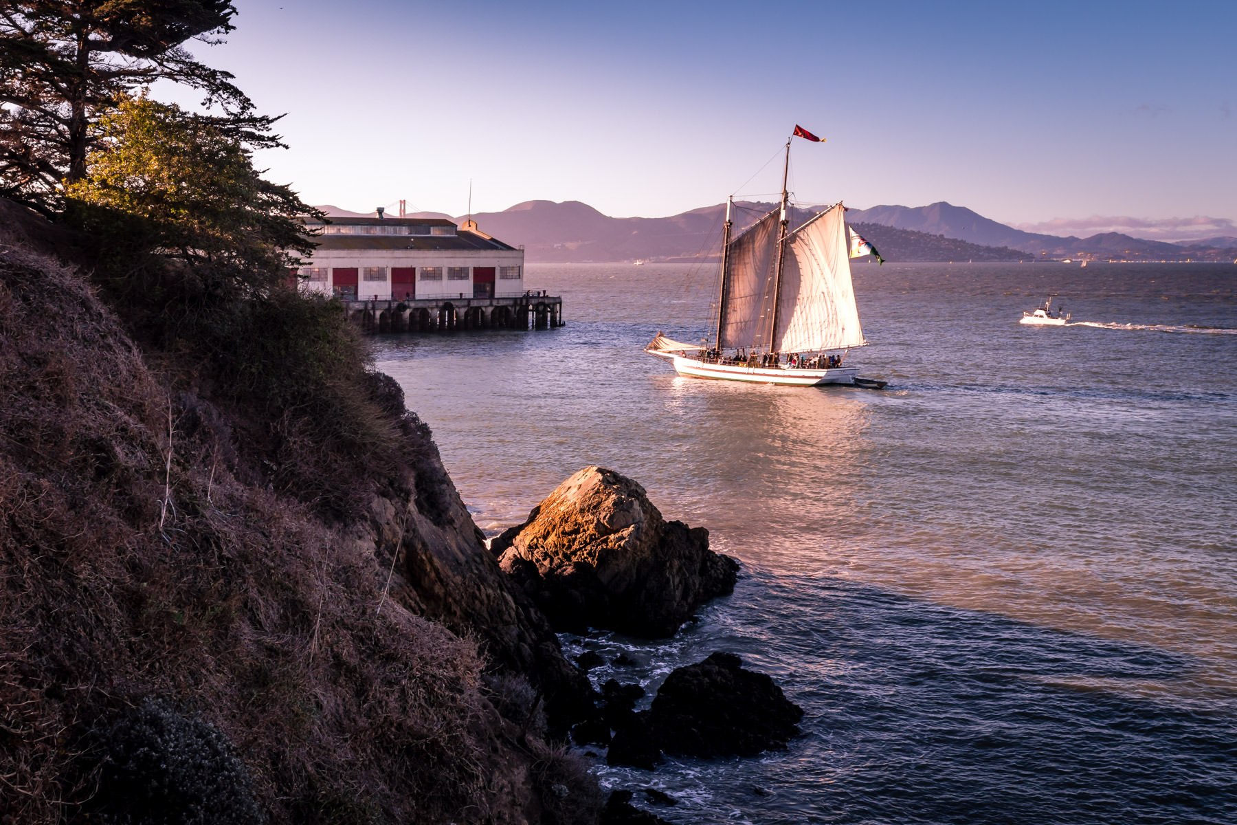 The 1891 scow schooner Alma, in the collection of the San Francisco Maritime National Historical Park, sails near the Festival Pavilion at the Fort Mason Center for Arts & Culture in San Francisco Bay.