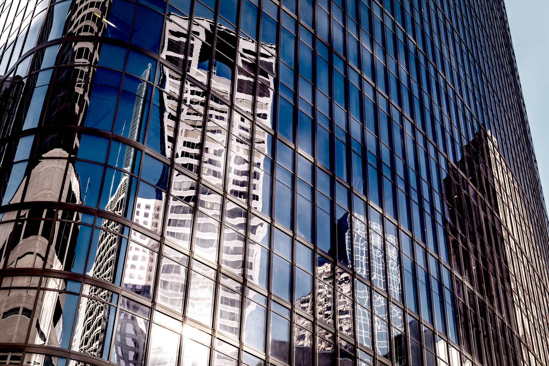 Adjacent skyscrapers are reflected in the glass facade of 1111 Travis Street in Downtown Houston.