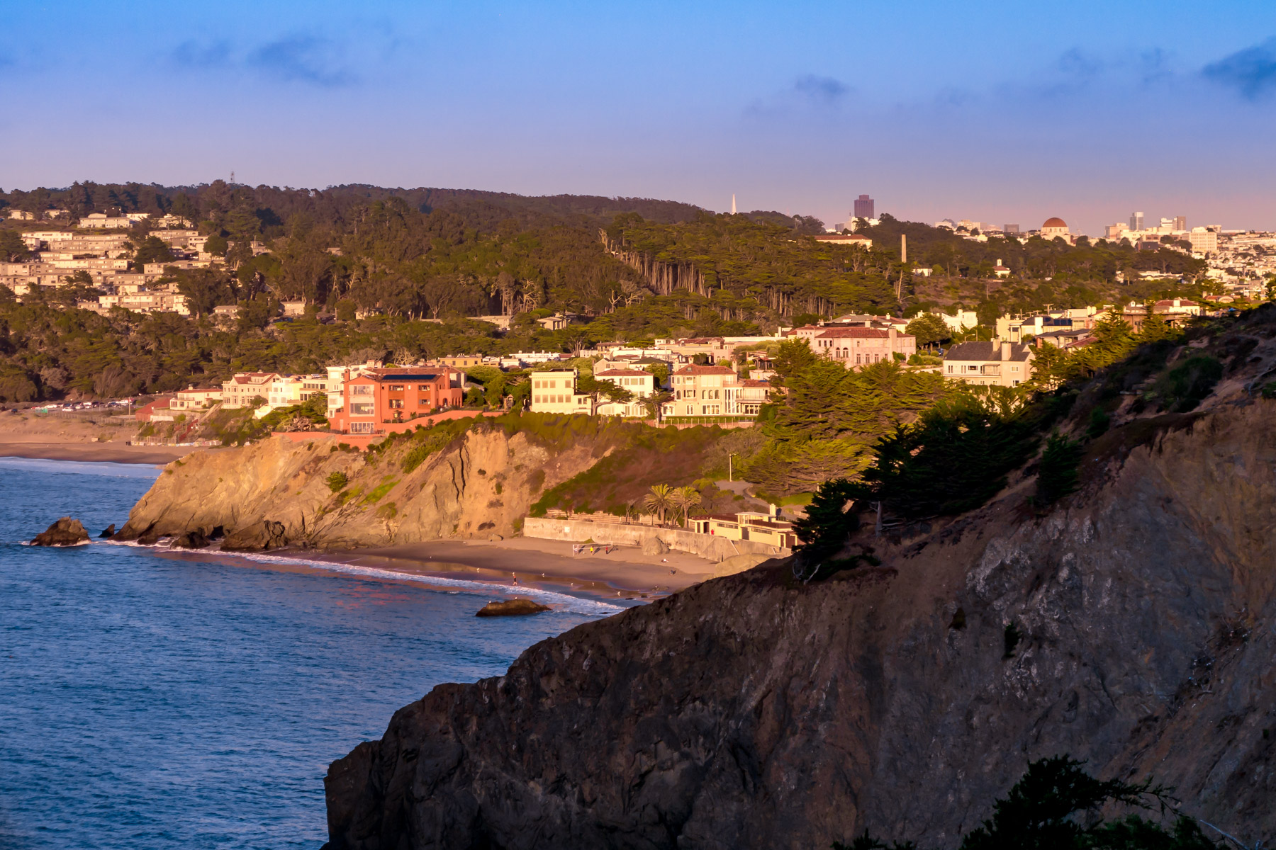 The late evening sun lights San Francisco's Sea Cliff neighborhood, China Beach and the buildings of the Presidio, as seen from the nearby Coastal Trail at Lands End.