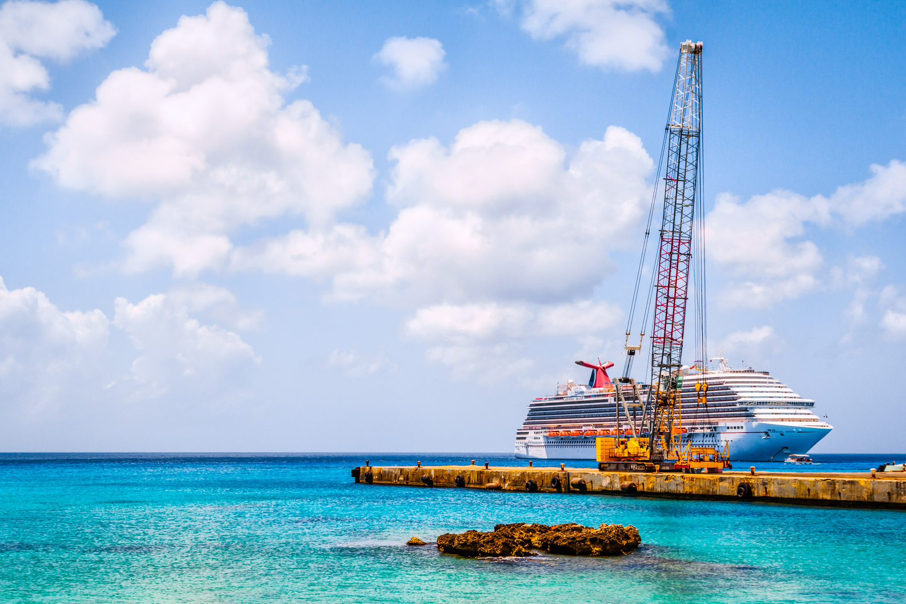 The cruise ship Carnival Magic is obscured by a crane on a nearby pier along the waterfront in George Town, Grand Cayman.