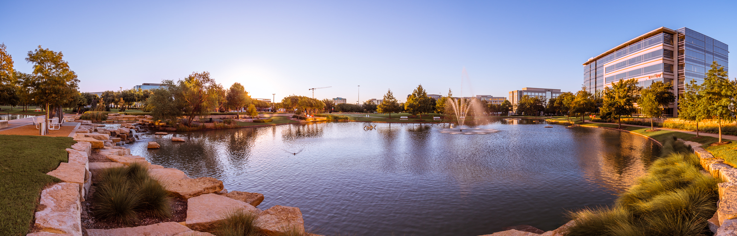 The morning sun illuminates the pond at Frisco, Texas' Hall Office Park.