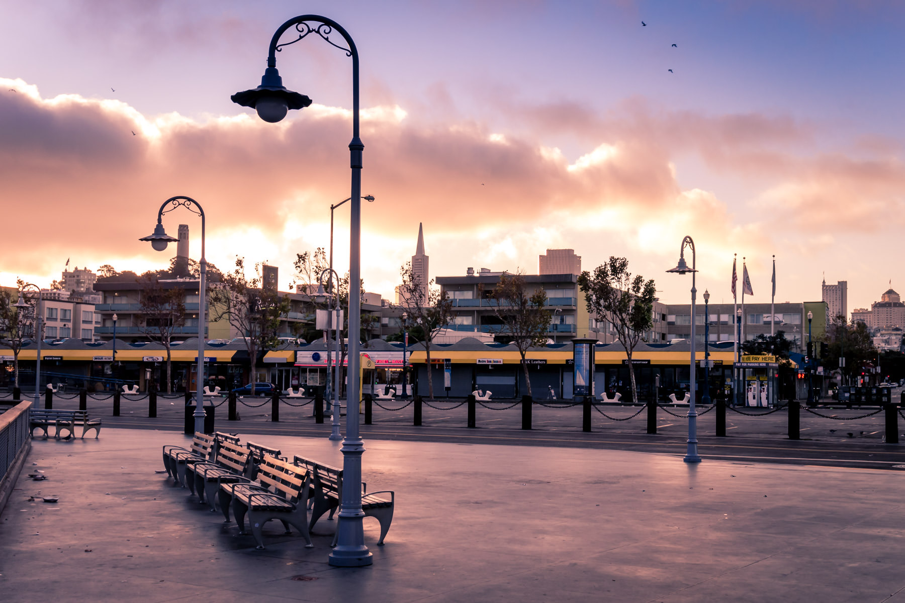 The sun rises over San Francisco, illuminating the empty streets of Fisherman's Wharf and the adjacent North Beach neighborhood.