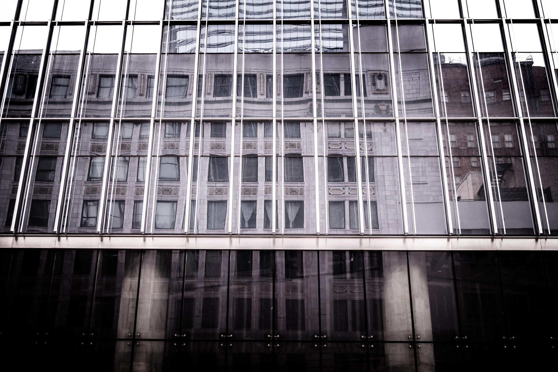 Adjacent buildings are reflected in the glass façade of Downtown Houston's 609 Main at Texas.