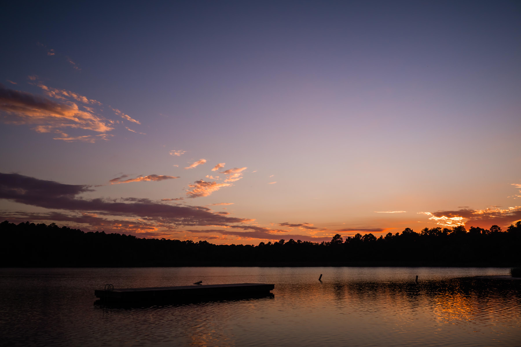 The sun sets on the tree-lined lake of Texas' Tyler State Park.