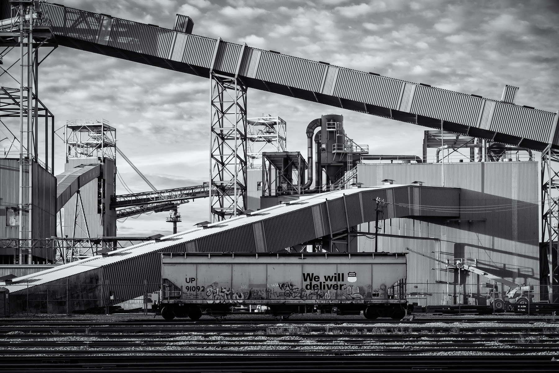 A Union Pacific hopper car is dwarfed by massive industrial equipment at the ADM Grain terminal at the Port of Galveston, Texas.