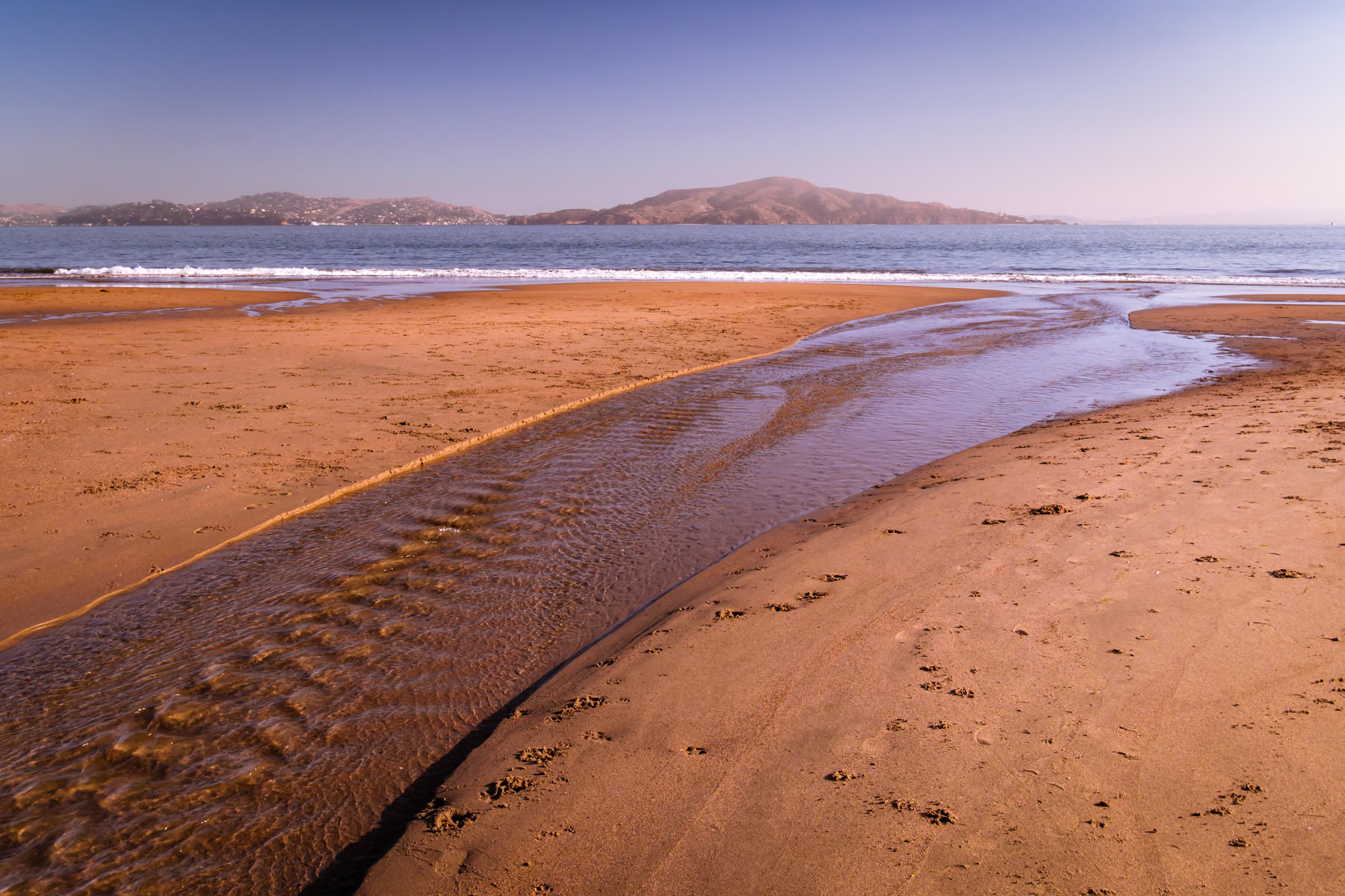 Early-morning waves from San Francisco Bay roll onto the shore at Crissy Field.