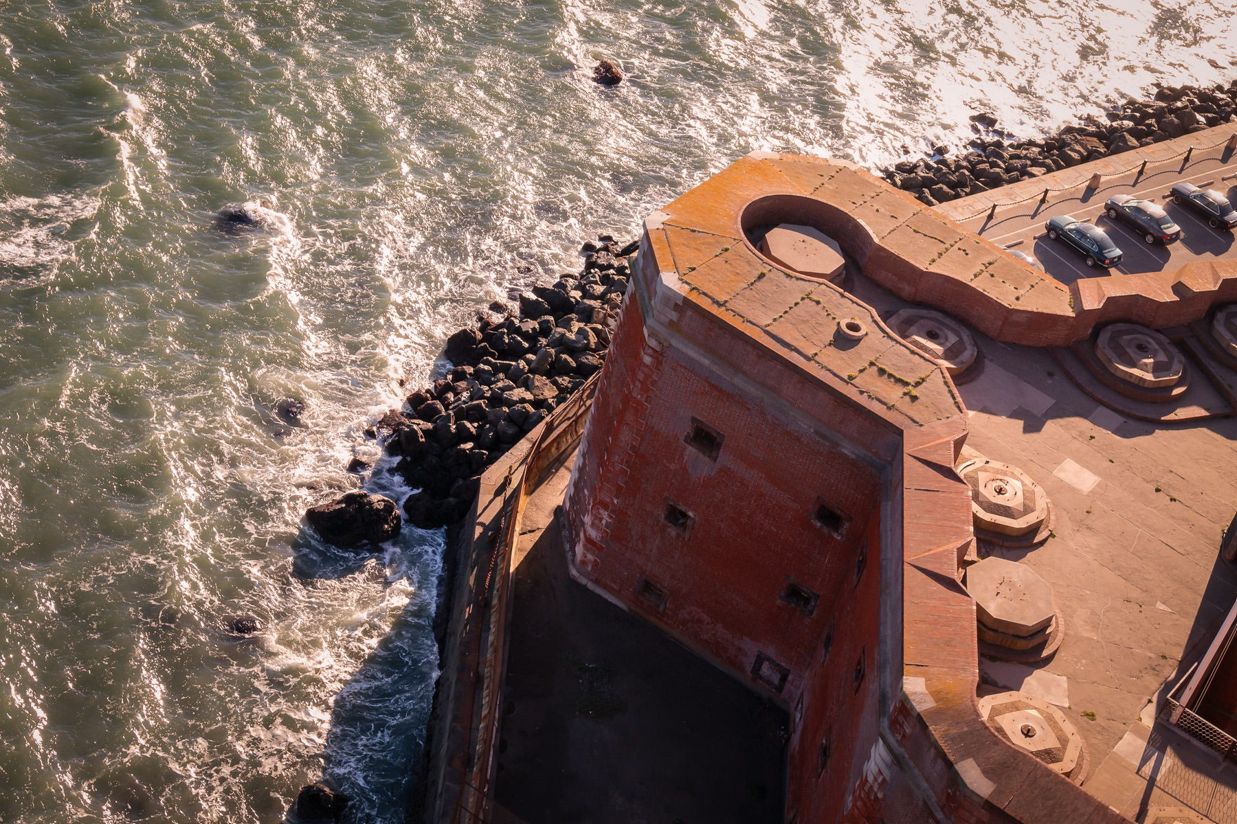 The surf of San Francisco Bay churns around the rocky shoreline at historic Fort Point, as seen from the pedestrian walkway on the Golden Gate Bridge.