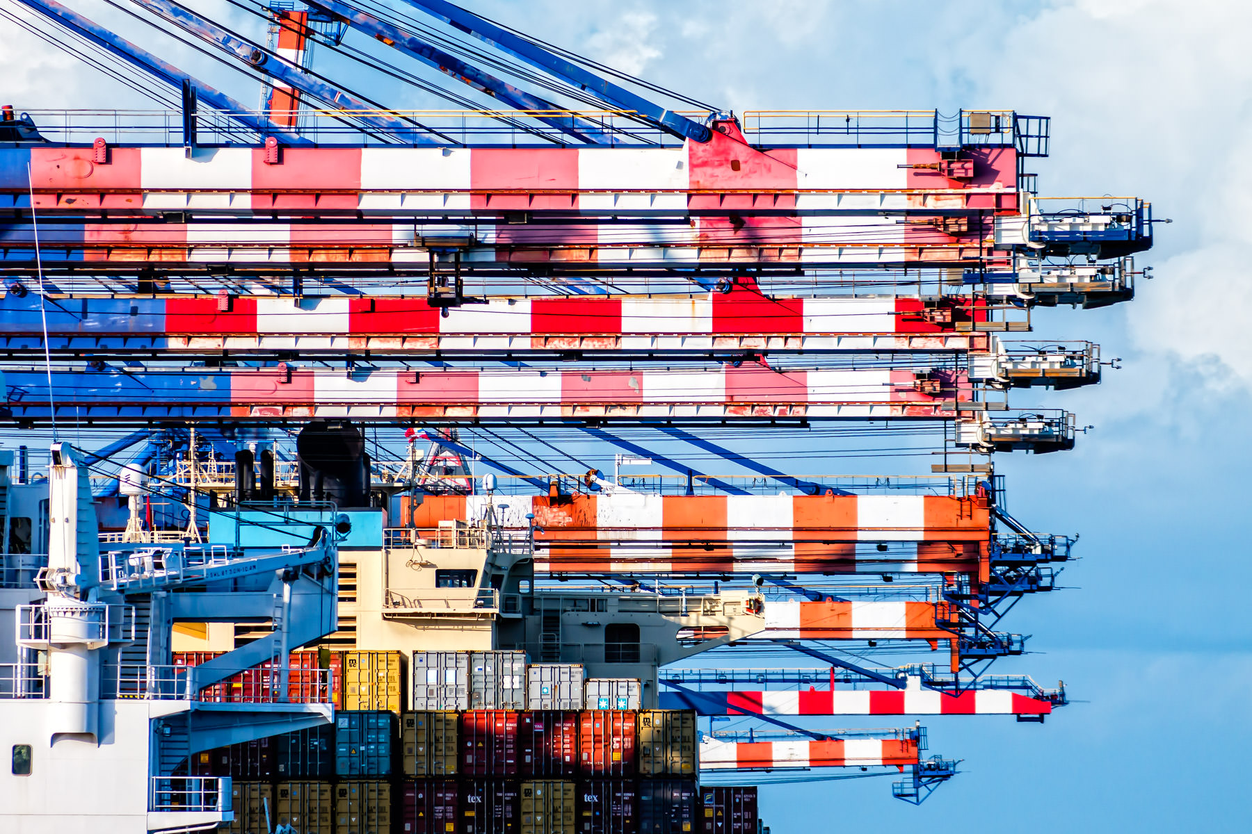 Peppermint-striped cranes load and unload cargo containers at Freeport, Bahamas.