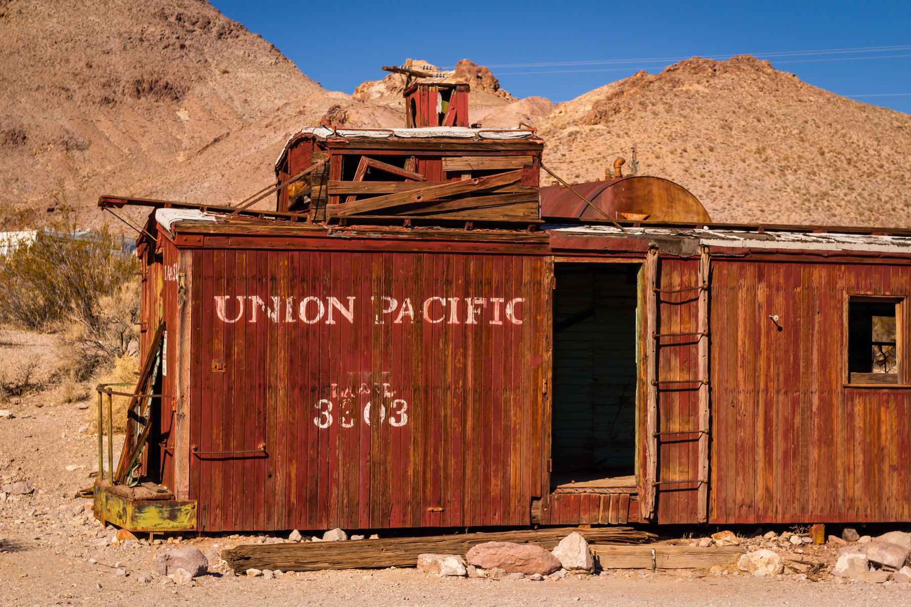 An abandoned Union Pacific boxcar lies weathered in the desert at the Nevada ghost town of Rhyolite.