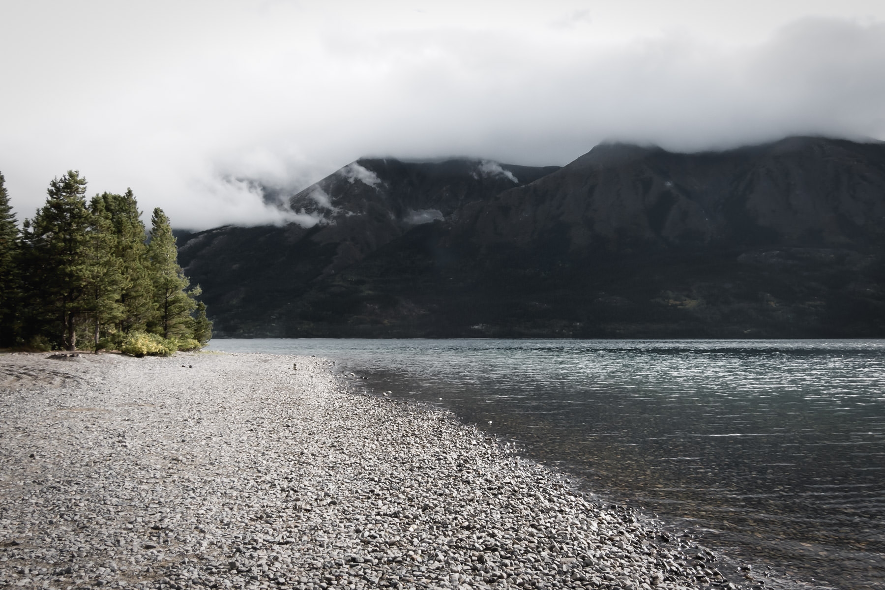 The cloudy, rocky shoreline of British Columbia's Tutshi Lake.