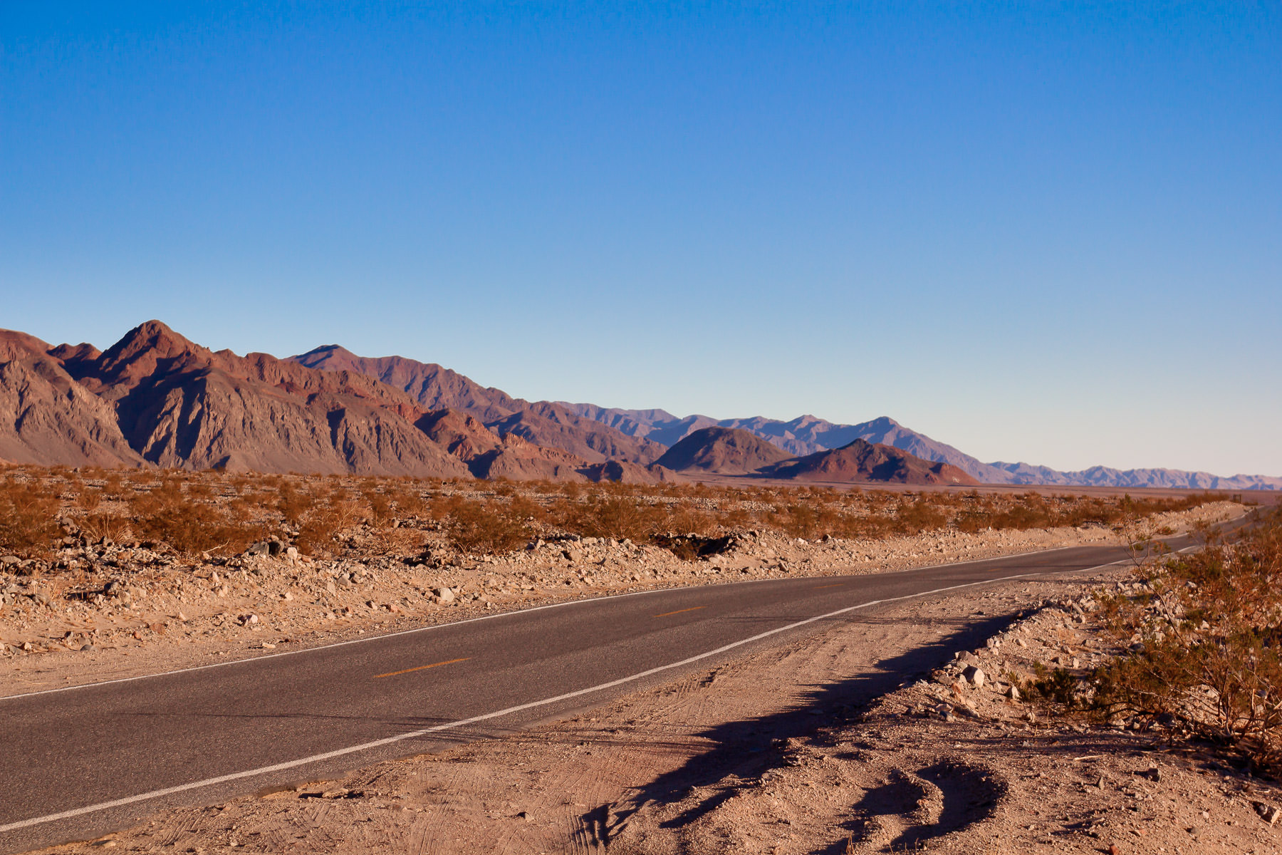 A lonely desert road leads through Death Valley National Park, California.
